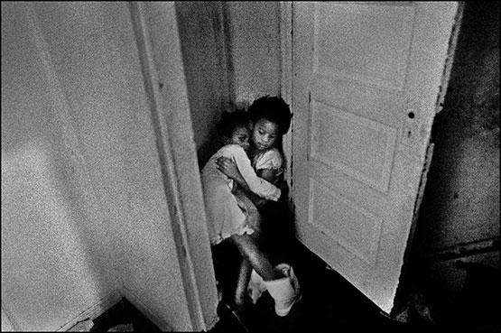© Justin Maxon. Jasmine Rasheed-Bacon, 6, consoles her cousin, Breonna Starkey-Bacon, 6, after she went into a closet to cry because of a disturbance in the house. The two cousins are very close and rely on each other for support. The girls live in a dangerous neighborhood called the Sun Village in Chester, PA, which is notorious for its drug trafficking and drug related crime.