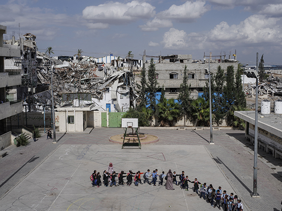 Gaza, Palestine. 2014. Schoolchildren head to class at the Sobhi Abu Karsh School in the Shujai'iya neighborhood. Operation Protective Edge lasted from 8 July 2014 – 26 August 2014, killing 2,189 Palestinians of which 1,486 are believed to be civilians. 66 Israeli soldiers and 6 civilians were killed. It's estimated that 4,564 rockets were fired at Israel by Palestinian militants. (Peter van Agtmael / Magnum Photos)