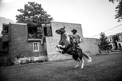 Seventeen-year-old Shahir Drayton rears back on a horse in a vacant Philadelphia lot. ©Charles Mostoller