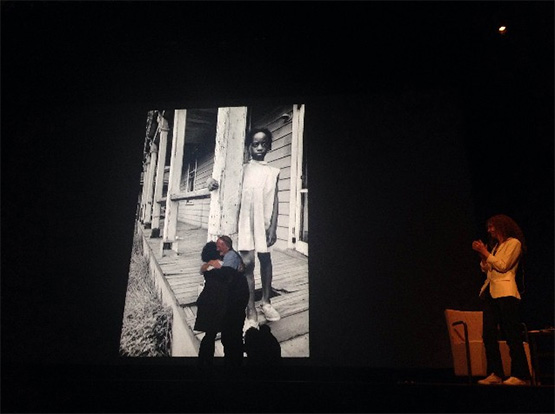David Alan Harvey greets Lois Liggins on stage at the the 2015 LOOK3 festival, in front of a portrait of Liggins that Harvey shot in 1966. ©Jessica Earnshaw