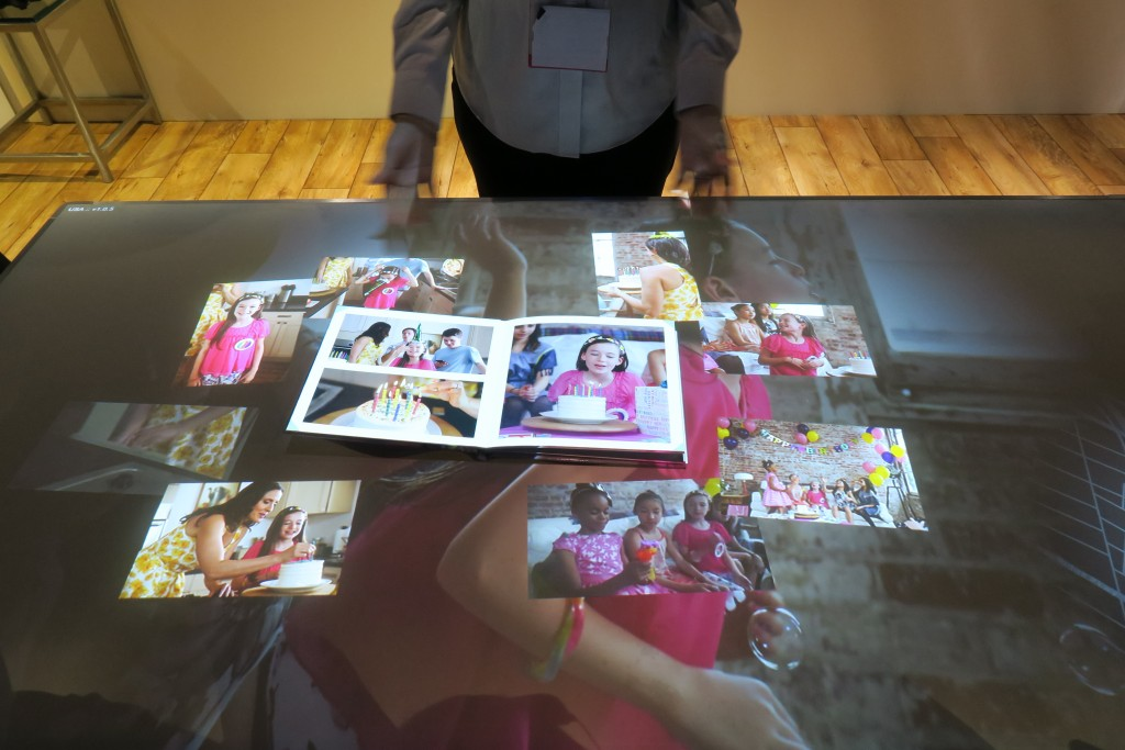 An analog photo book comes to live as similarly tagged images and videos are pulled down from the cloud to the smart table.