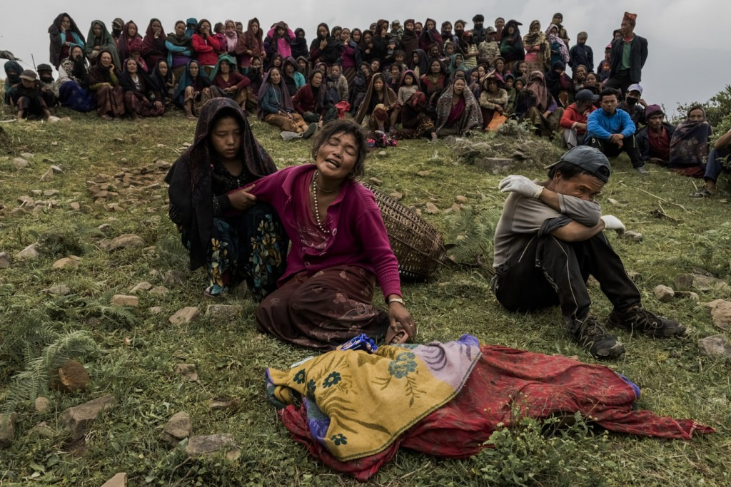 Bishnu Gurung (C) weeps as the body of her daughter, Rejina Gurung, 3, recovered from the rubble of her earthquake destroyed home, lays covered by cloth during her funeral on May 8, 2015 in the village of Gumda, Nepal. Neighbours discovered the body of the small girl in the rubble of the entrance of the family home, ending a 13 day search for Rejina in the remote mountain side village of Gumda in Gorkha district. On the 25th of April, just before noon local time, as farmers were out in fields and people at home or work, a devastating earthquake struck Nepal, killing over 8,000 people and injuring more than 21,000 according to the United Nations Office for the Coordination of Humanitarian Affairs. Homes, buildings and temples in Kathmandu were destroyed in the 7.8 magnitude quake, which left over 2.8 million people homeless, but it was the mountainous districts away from the capital that were the hardest hit. Villagers pulled the bodies of their loved ones from the rubble by hand and the wails of grieving families echoed through the mountains, as mothers were left to bury their own children. Over the following weeks and months, villagers picked through ruins desperate to recover whatever personal possessions they could find and salvage any building materials that could be reused. Despite relief teams arriving from all over the world in the days after the quake hit, thousands of residents living in remote hillside villages were left to fend for themselves, as rescuers struggled to reach all those affected. Multiple aftershocks, widespread damage and fear kept tourists away from the country known for its searing Himalayan peaks, damaging a vital climbing and trekking industry and compounding the recovery effort in the face of a disaster from which the people of Nepal continue to battle to recover.