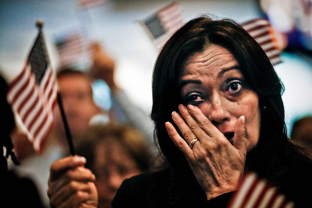 """Olga Riano wipes tears from her eyes as she and her fellow newly naturalized American citizens sing along to the song, """"Proud To Be An American,"""" by Lee Greenwood during a Naturalization Ceremony for 51 people from 20 different countries at Hodges University in Naples on Thursday, November 12, 2015. """"It's my big day,"""" said Riano, who's originally from Colombia, """"I'm happy to be in this country. I'm free."""""""