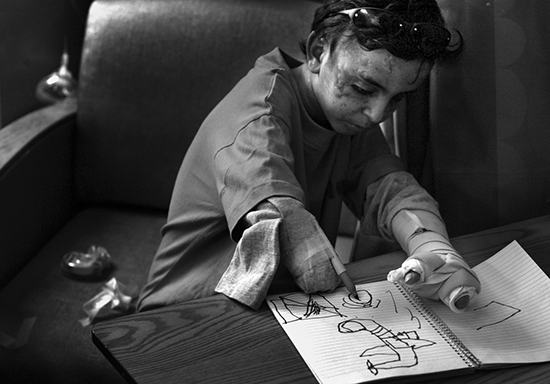 Saleh draws an airplane dropping bombs, after nurses taped a felt-tipped pen to his arm in an effort to soothe him. ©Deanne Fitzmaurice